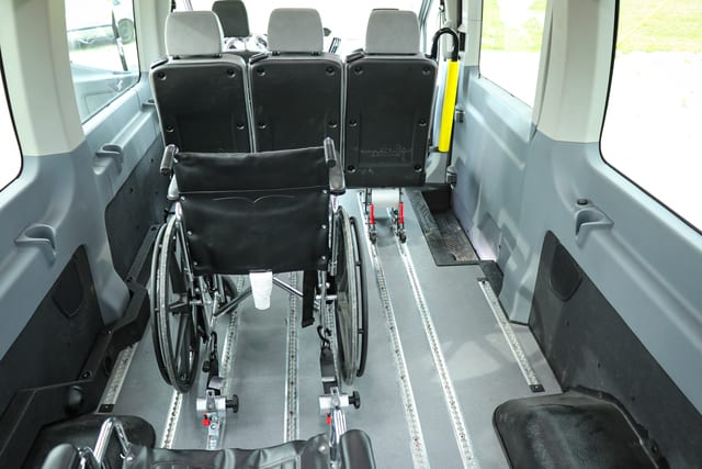 wheelchair restraints holding down a wheelchair in a Ford Transit accessible mobility van for disabled transportation