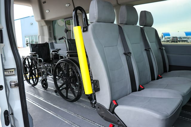 three removeable seats and two wheelchairs secured in a Ford Transit wheelchair van converted at MoveMobility in winnipeg