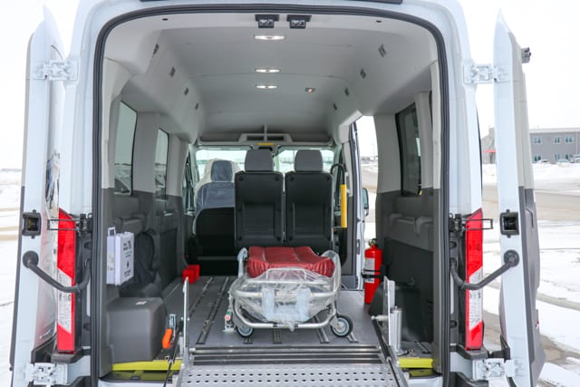White Ford Transit van with passenger seats, floor track system and stretcher for medical transportation