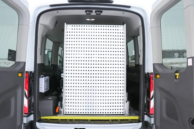 rear access wheelchair ramp folded up in the back of a Ford Transit van