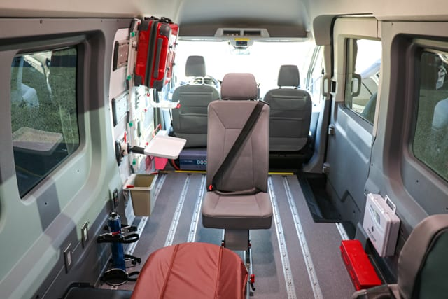 BraunAbility hydraulic lift at the back of a ram promaster wheelchair van, lifting a wheelchair into the van for transport