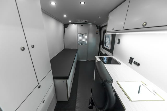 Interior view of Ford Transit medical van with patient bed, storage, desk, workstation, office chair