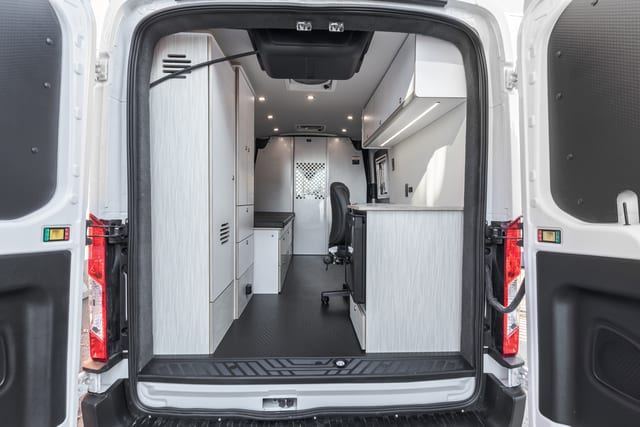 Rear view of Ford Transit medical health van for mobile doctor's office, with office chair, desk, storage, non slip flooring, and patient bed